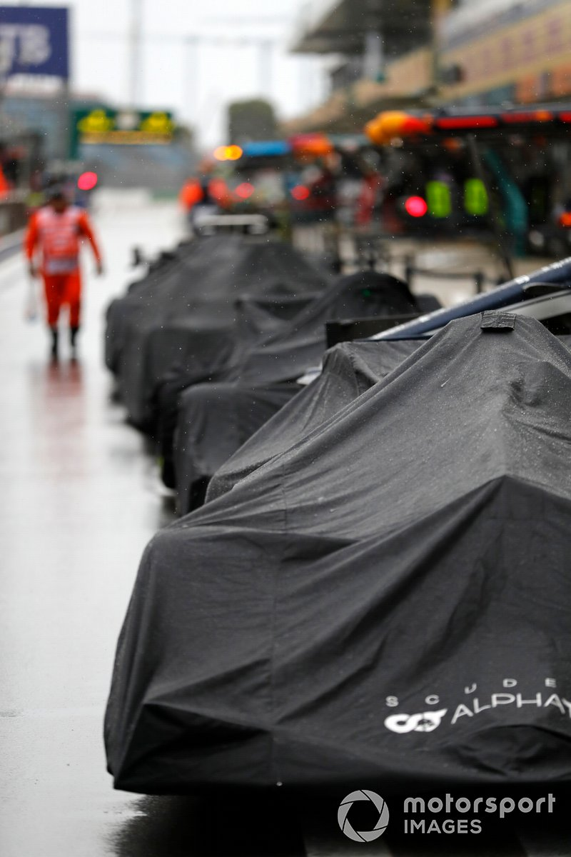 Coches cubiertos por la lluvia en el pit lane