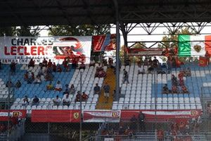 Fans in a grandstand show support for Charles Leclerc, Ferrari