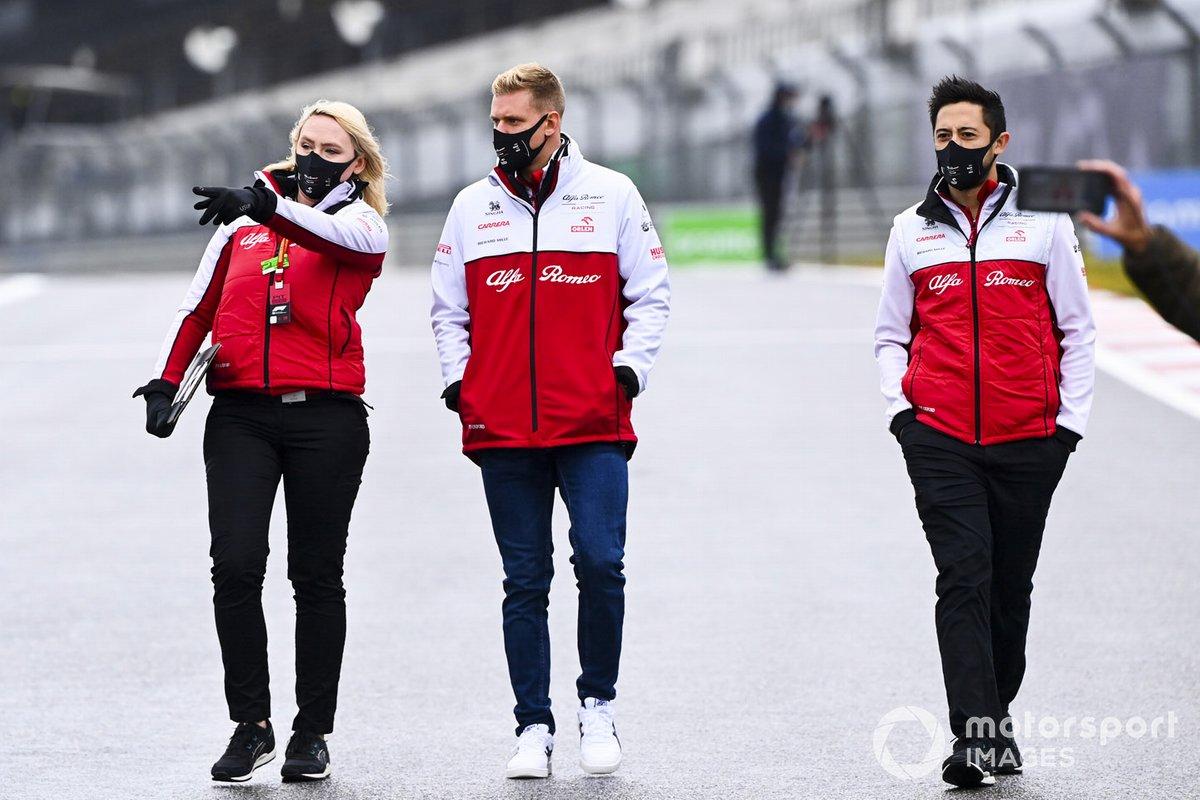 Mick Schumacher, Alfa Romeo, recorre la pista con miembros del equipo
