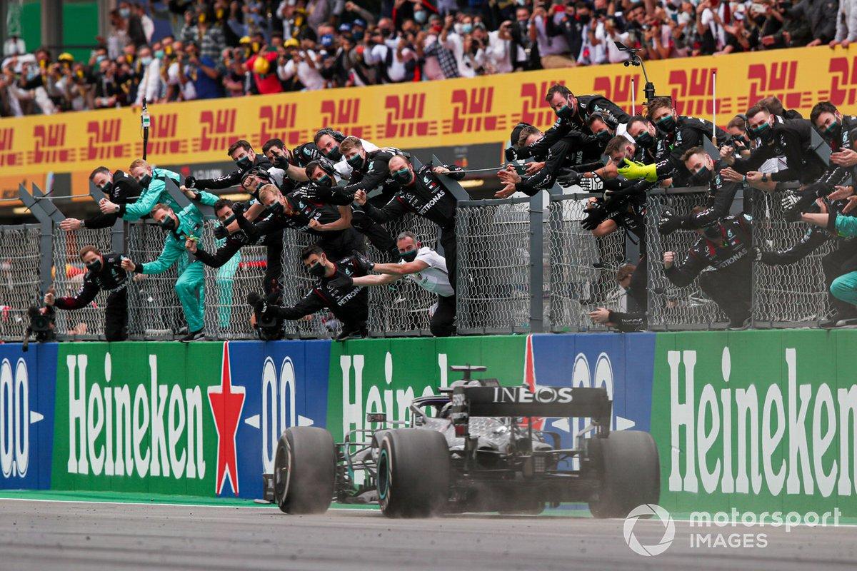 Lewis Hamilton, Mercedes F1 W11, 1ª posición, cruza la línea para el deleite de su equipo en el pit wall