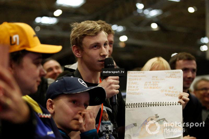 A fan shows Lando Norris his notebook during a Q&A session