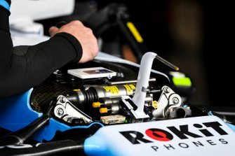 A mechanic wrks on the suspension of the Williams FW42