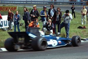 Photographers standing close to action of Jackie Stewart, Tyrrell 003 Ford
