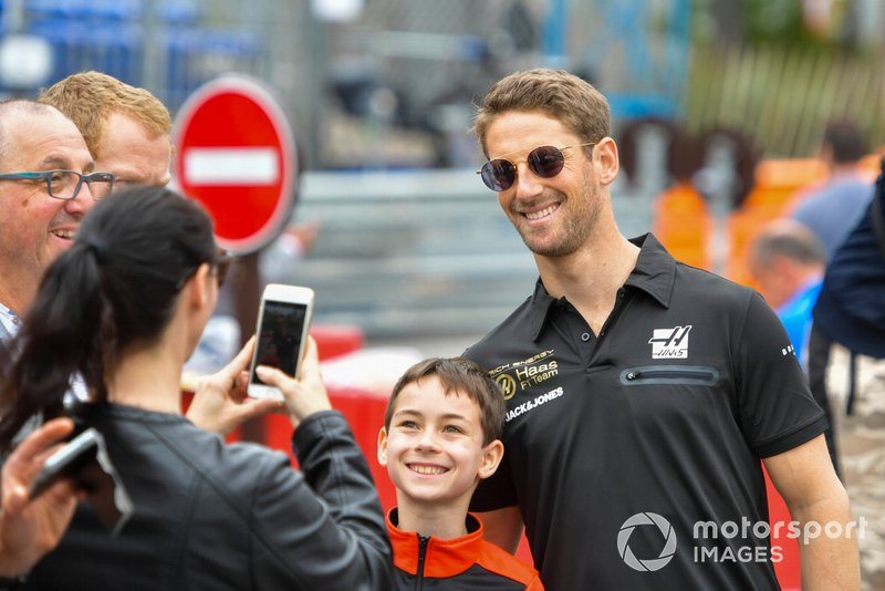 Romain Grosjean, Haas F1 poses for a photograph with a young fan