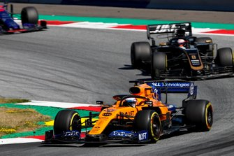 Carlos Sainz Jr., McLaren MCL34, leads Romain Grosjean, Haas F1 Team VF-19