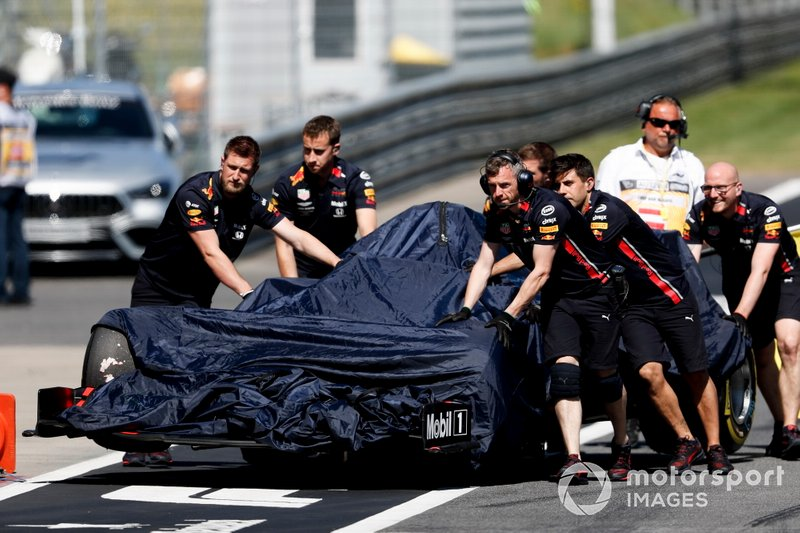 Car of Max Verstappen, Red Bull Racing RB15 being pushed down the pit lane by mechanics after his crash