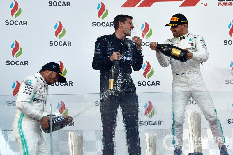 Lewis Hamilton, Mercedes AMG F1, 2nd position, and Valtteri Bottas, Mercedes AMG F1, 1st position, spray Champagen at their team mate on the podium