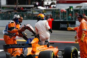 Fernando Alonso, McLaren MCL33, exits his car after crashing over Charles Leclerc, Sauber C37, following contact from Nico Hulkenberg, Renault Sport F1 Team R.S. 18, at the start