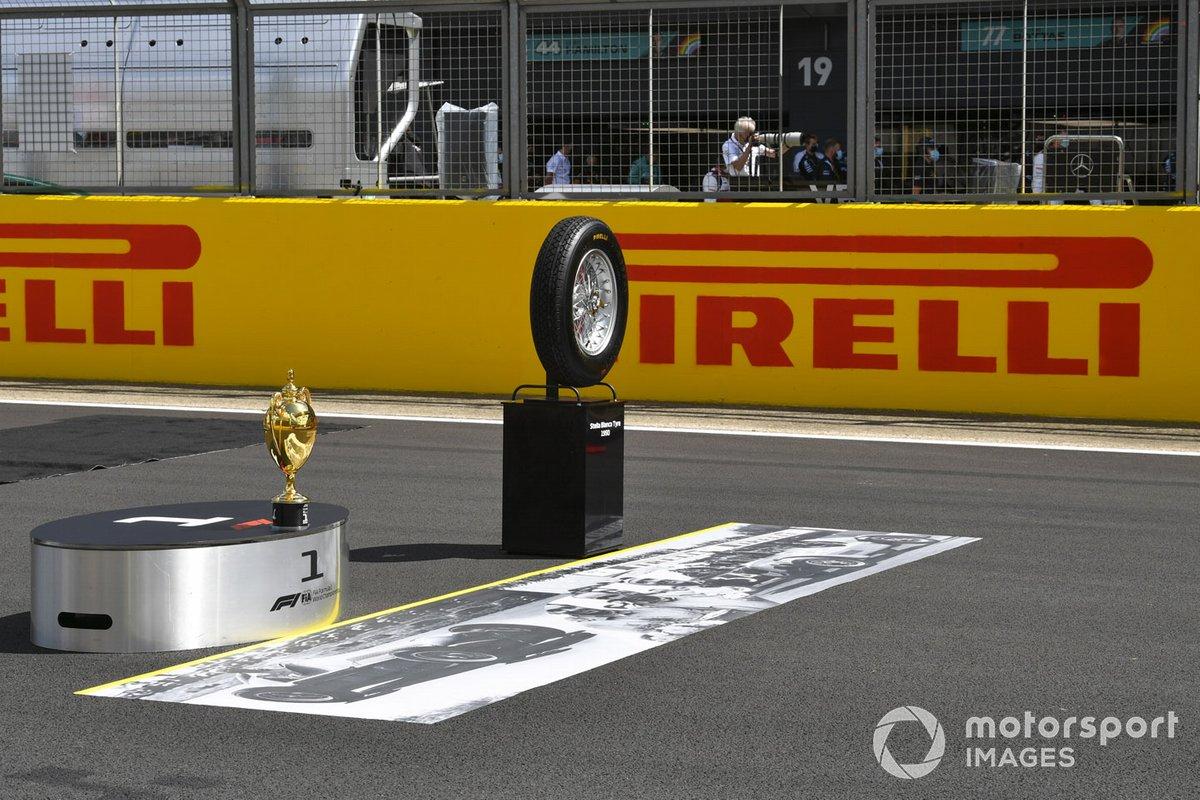 El trofeo y un neumático de la primera carrera en la parrilla antes de la salida