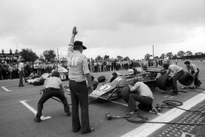Ken Tyrrell, Tyrrell Team Owner holds Jody Scheckter, Tyrrell 007 as the team competes in a pit stop tyre change competition against McLaren