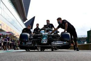 Механики толкают Mercedes F1 W11 Льюиса Хэмилтона по пит-лейну