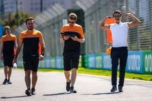 Lando Norris, McLaren and members of the team walk the track