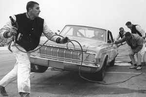 Maurice Petty loops the air hose around his brother Richard Petty's racecar during a pit stop