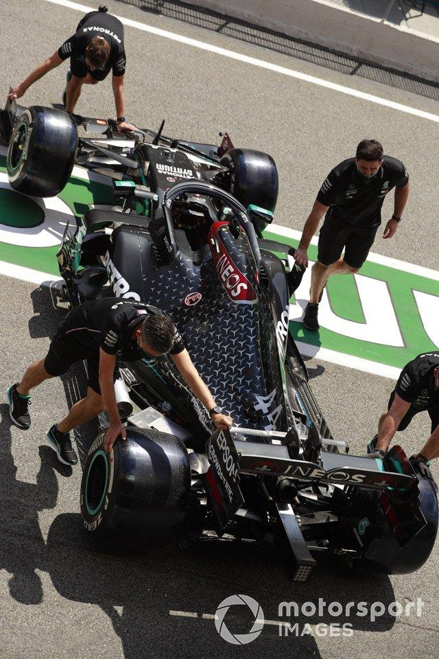 Los mecánicos empujan el monoplaza de Lewis Hamilton, Mercedes F1 W11 EQ Performance, en el pit lane