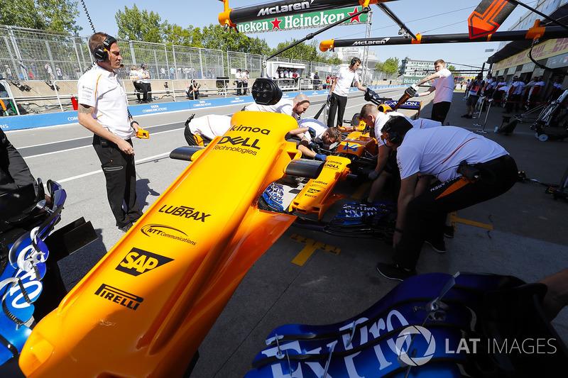 Les mécaniciens travaillent sur la voiture de Fernando Alonso McLaren MCL33 dans la voie des stands, et enlèvent le nez de la voiture