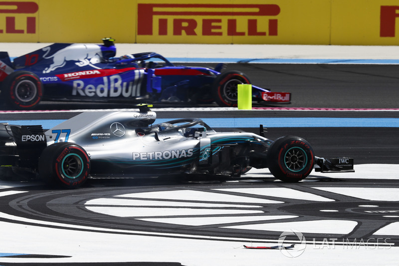 Pierre Gasly, Toro Rosso STR13, passes as Valtteri Bottas, Mercedes AMG F1 W09, recovers from an incident at the start