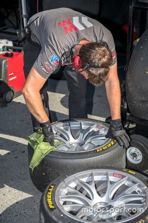 A team member works on tires and rims