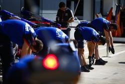 Toro Rosso mechanics perform stretching exercises