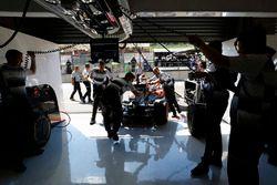 Team members wheel Jenson Button, McLaren into the garage.
