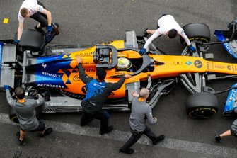 Lando Norris, McLaren MCL34, is returned to the garage