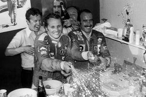 Niki Lauda festeggia con il vincitore della gara e compagno di squadra in Ferrari, Clay Regazzoni nella hospitality Ferrari