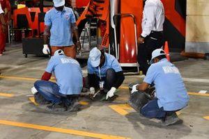 Maintenance men work on the pit lane floor outside the Ferrari garage