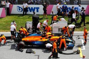 Lando Norris, McLaren, gets ready as his team prepare his car on the grid