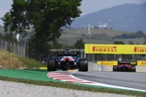 Sparks kick up from the rear of Fernando Alonso, Alpine A521