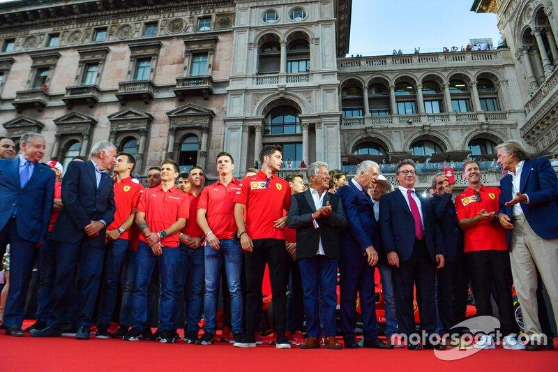 Charles Leclerc, Ferrari, Mario Andretti, and Piero Lardi Ferrari stand amongst the Ferrari Academy drivers and former Ferrari F1 drivers and team personnel