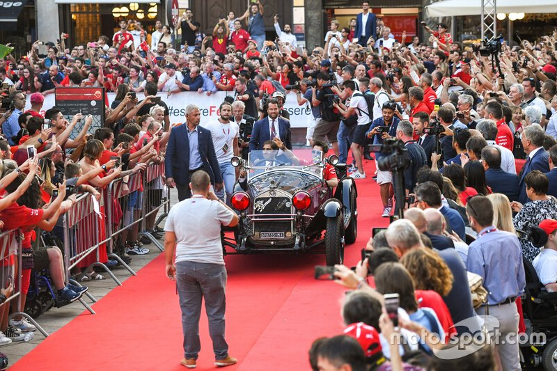 Charles Leclerc, Ferrari waves to the crowd from the passenger seat of a classic Alfa Romeo