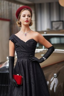 A model in 1950s period fashion poses during a photoshoot with a Rolls Royce