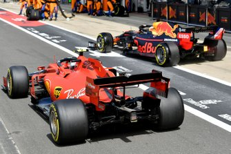 Max Verstappen, Red Bull Racing RB15, and Charles Leclerc, Ferrari SF90, race to be first out of the pit lane
