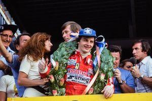 Gilles Villeneuve, Ferrari celebra la victoria en el podio mientras Jackie Stewart transmite