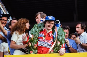 Gilles Villeneuve, Ferrari celebrates victory on the podium as Jackie Stewart broadcasts