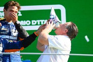 Zak Brown, CEO, McLaren Racing, drinks from the shoe of Daniel Ricciardo, McLaren, 1st position, on the podium as Lando Norris, McLaren, 2nd position, looks on