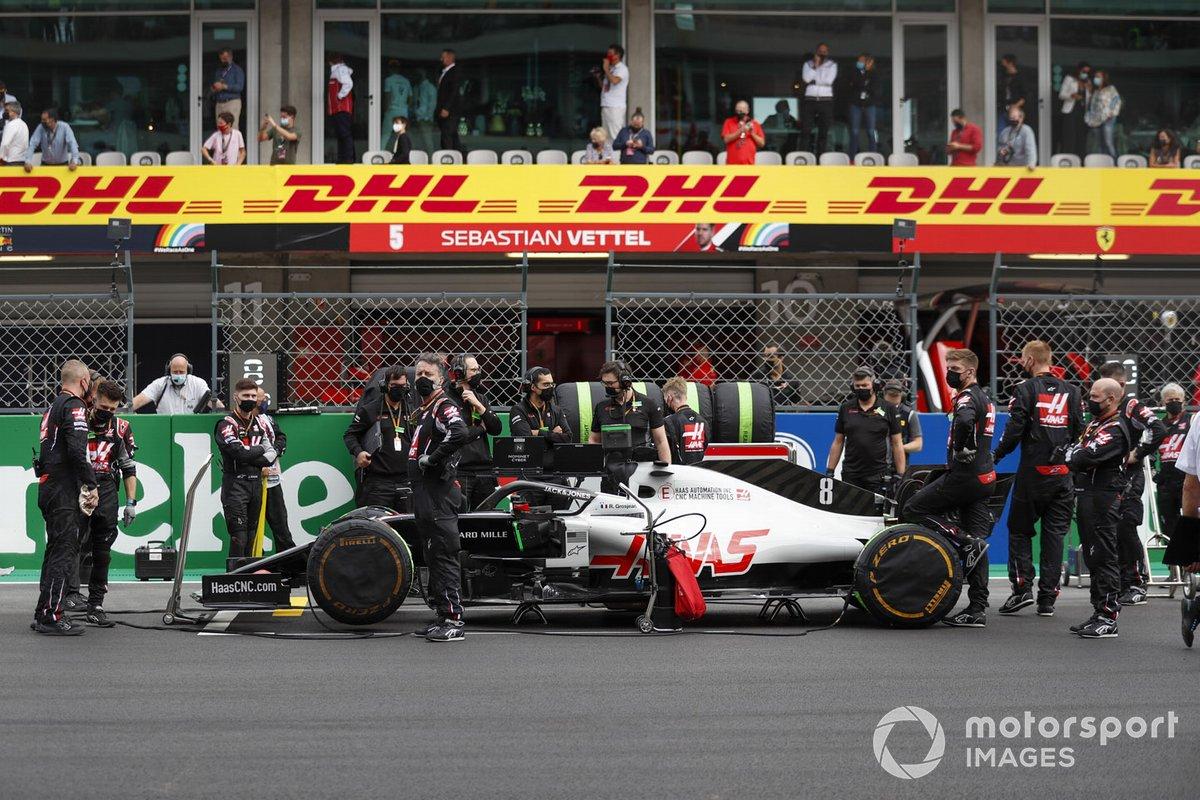 Los mecánicos de Haas F1 en la parrilla con el coche de Romain Grosjean, Haas VF-20