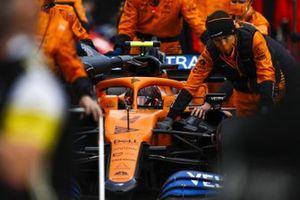 Lando Norris, McLaren MCL35, is brought to the grid by mechanics