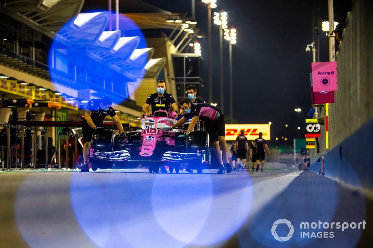 Los mecánicos empujan el Racing Point RP20 de Sergio Pérez a lo largo del pitlane