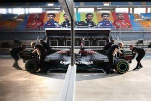 Mechanics move the car of Lewis Hamilton, Mercedes F1 W11, in the pit lane