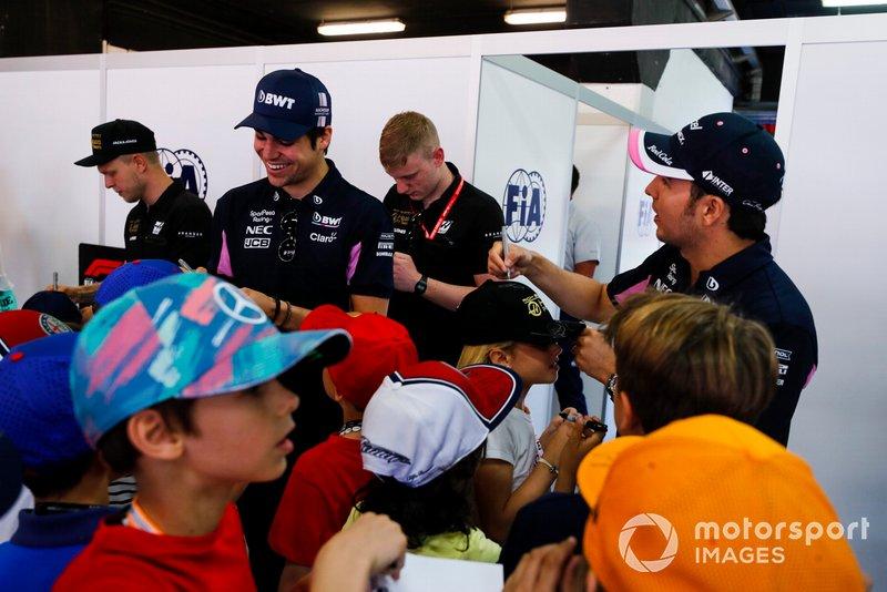 Kevin Magnussen, Haas F1, Lance Stroll, Racing Point, y Sergio Pérez, Racing Point, firman autógrafos para los jóvenes aficionados