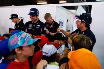 Kevin Magnussen, Haas F1, Lance Stroll, Racing Point, and Sergio Perez, Racing Point, sign autographs for young fans