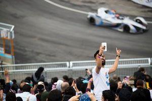 Un fan prend un selfie avec les voitures en piste