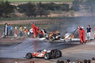 John Surtees, McLaren M7C-Ford, pasa por delante de los coches envueltos en llamas de Jacky Ickx y Jackie Oliver