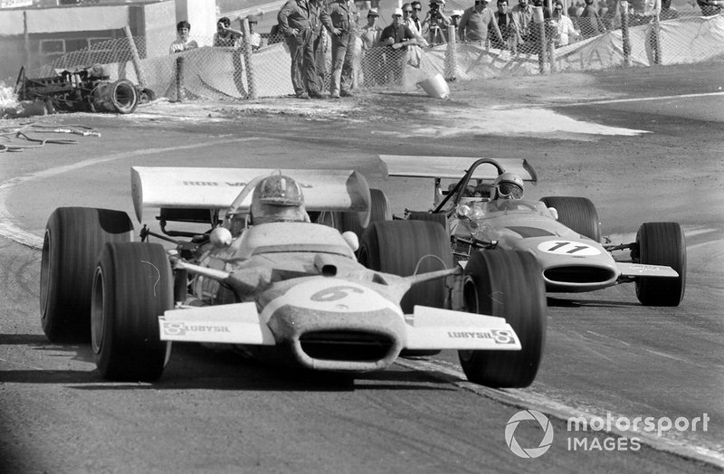 Graham Hill, Lotus 49C Ford, leads Bruce McLaren, McLaren M14A Ford, pasan a los oficiales que trabajan para retirar un coche quemado