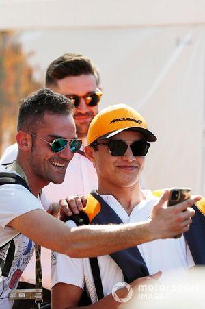 Lando Norris, McLaren, poses for a selfie with a fan