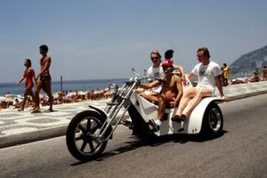 Ronnie Peterson, Lotus, Patrick Tambay, McLaren; and Didier Pironi, Tyrrell enjoy a ride beside the beach on an outlandish motorbike