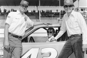 Petty Enterprises crew chief Dale Inman sits in the racecar as brothers Maurice Petty and Richard Petty pose at a NASCAR Cup race