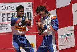 Kush Maini and Lorenzo Colombo celebrate with champagne on the podium