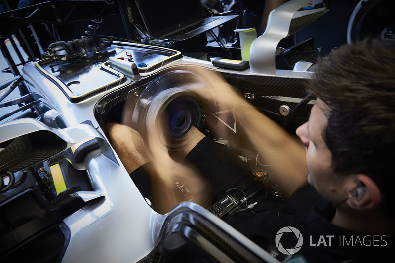 Mercedes mechanic in the cockpit of a Mercedes AMG F1 W08