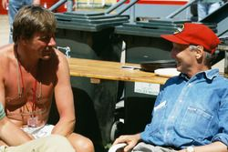Former World Champions, James Hunt and Niki Lauda chat in the paddock